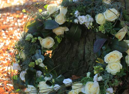 A wreath leaning against the trunk of a tree